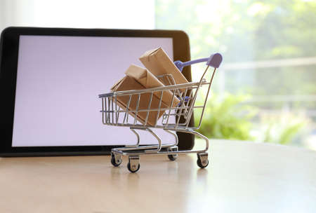 Internet shopping. Small cart with boxes near modern tablet on table indoors