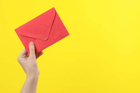 Woman holding red paper envelope on yellow background, closeup. Space for text Stok Fotoğraf