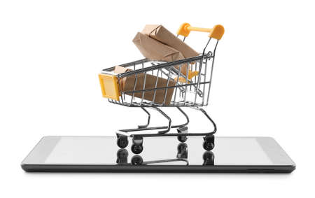 Internet shopping. Small cart with boxes and modern tablet on white background
