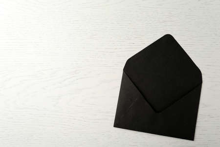 Black paper envelope on white wooden background, top view. Space for text Stok Fotoğraf