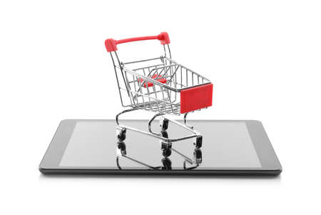Internet shopping. Small cart and modern tablet on white background