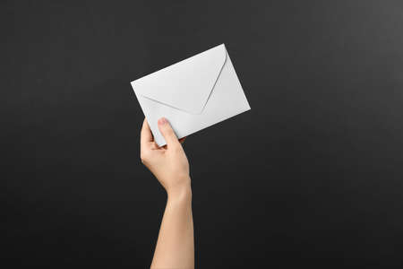 Woman holding white paper envelope on black background, closeup