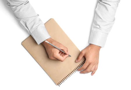 Man with pencil and notepad on white background, top view. Closeup of hands Stockfoto