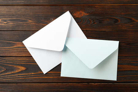White paper envelopes on wooden background, flat lay