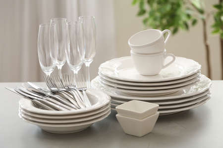 Set of clean dishware, cutlery and champagne glasses on table indoors Imagens