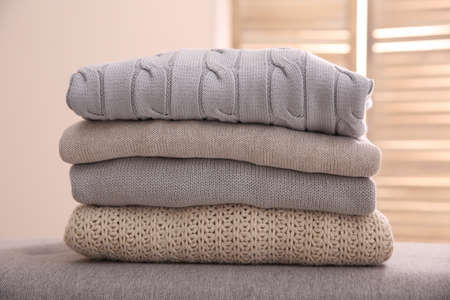 Stack of folded warm sweaters against blurred background