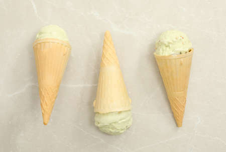 Delicious pistachio ice cream in wafer cones on light gray table, flat lay Imagens