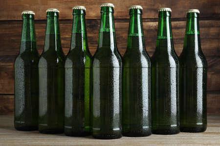 Green bottles of beer on wooden table Imagens