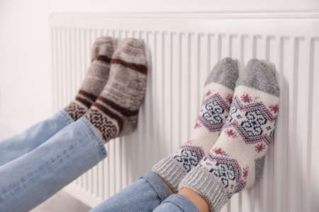Couple warming legs on heating radiator indoors, closeup