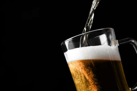 Pouring cold tasty beer into glass mug on black background, closeup. Space for text