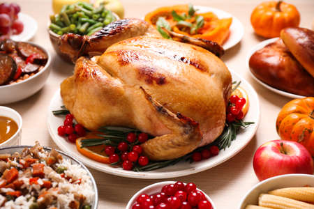 Traditional Thanksgiving day feast with delicious cooked turkey and other seasonal dishes served on wooden table