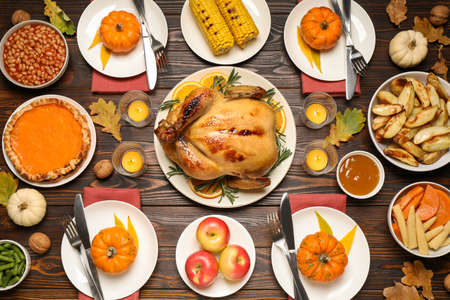 Traditional Thanksgiving day feast with delicious cooked turkey and other seasonal dishes served on wooden table, flat lay