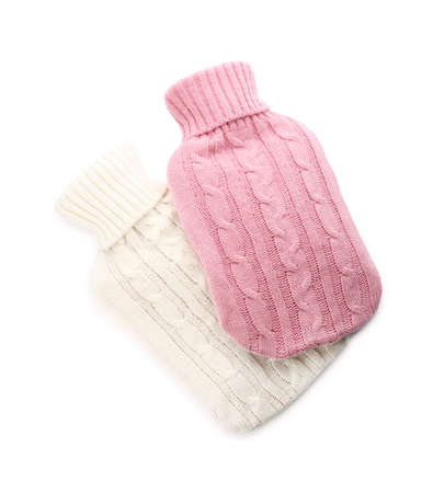 Hot water bottles with knitted covers isolated on white, top view