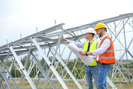 Professional engineers working on installation of electrical substation outdoors Stockfoto