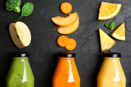 Flat lay composition with bottles of delicious juices and fresh ingredients on black table