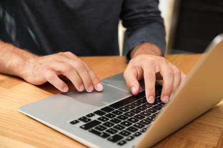 Man using laptop for search at wooden table, closeup