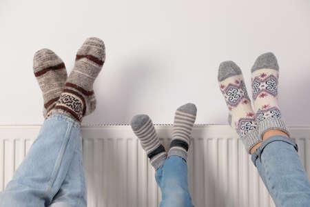 Family warming legs on heating radiator near white wall, closeup Stockfoto