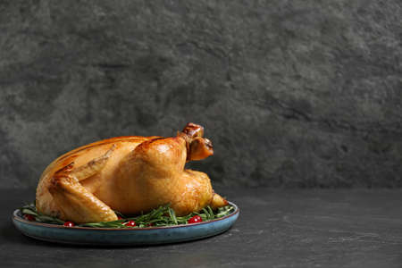 Delicious cooked turkey served with rosemary and cranberries on black table, space for text. Thanksgiving Day celebration