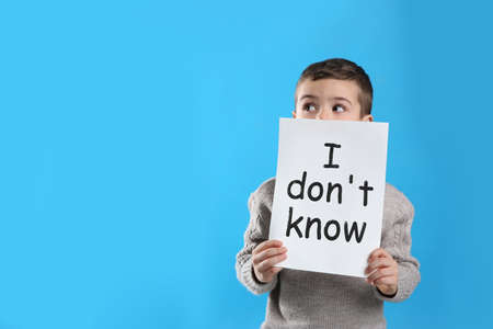 Emotional little boy holding paper with text I Don't Know on light blue background