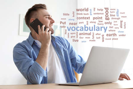 Young man talking on mobile phone while working with laptop at desk, word cloud in front of him