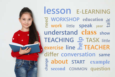 Cute little girl reading vocabulary on white background with word cloud