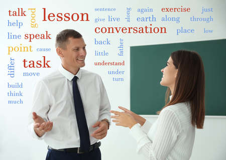 English teacher talking with student surrounded by different words near green chalkboard