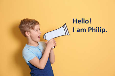 Cute little boy saying Hello! I Am Philip using paper megaphone on yellow background 免版税图像