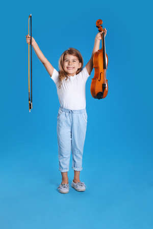 Little girl with violin and bow on light blue background Standard-Bild