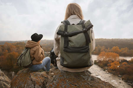 Group of friends with backpacks near mountain river, back view