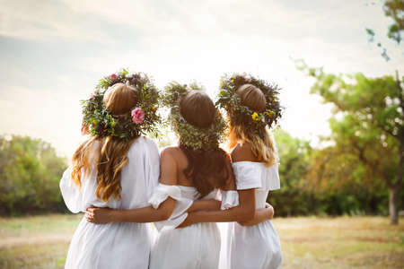 Young women wearing wreaths made of beautiful flowers outdoors on sunny day, back view