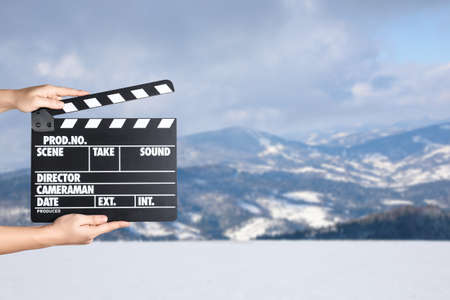 Assistant holding clapperboard outdoors, closeup. Cinema production