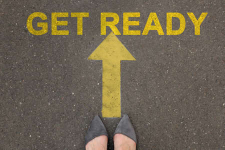 Text Get Ready and arrow on asphalt in front of woman, top view