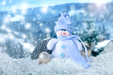 Cute toy snowman with Christmas balls in winter forest