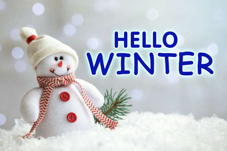 Greeting card with text Hello Winter. Little toy snowman and branch of fir tree on snow against blurred Christmas lights Stock Photo