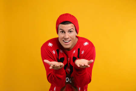 Emotional man in Christmas sweater and hat on yellow background Stock Photo