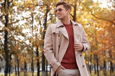 Handsome man walking in park on autumn day