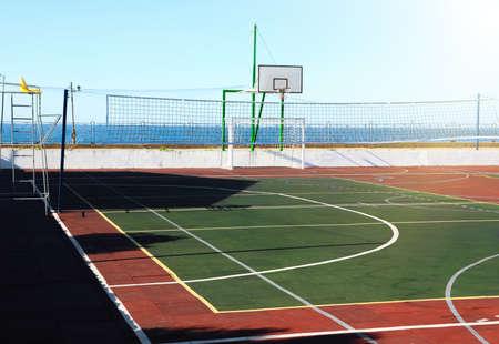 Empty multi-sport game court near sea on sunny day