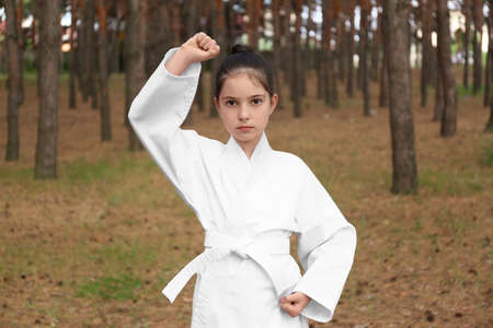 Cute little girl in kimono practicing karate in forest