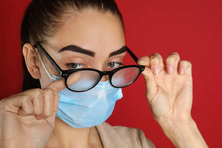 Woman wiping foggy glasses caused by wearing medical mask on red background, closeup