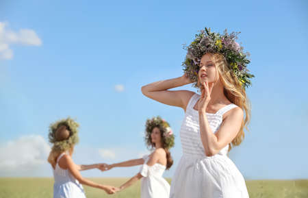 Young women wearing wreaths made of beautiful flowers in field on sunny day