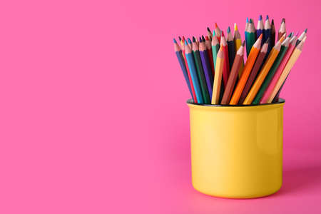 Colorful pencils in mug on pink background. Space for text Foto de archivo