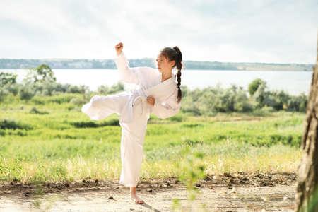 Cute little girl in kimono practicing karate outdoors