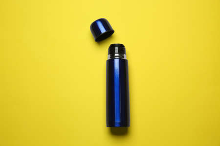 Blue metal thermos on yellow background, top view