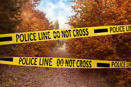 Yellow police tape isolating crime scene. Restricted area of autumn park