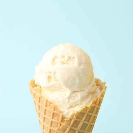 Delicious ice cream in waffle cone on light blue background, closeup Banque d'images