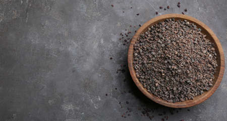 Black salt in wooden bowl on gray table, top view. Space for text