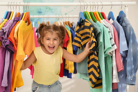 Funny little girl choosing clothes on rack indoors