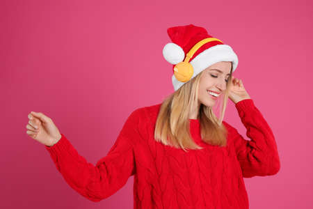 Happy woman with headphones on pink background. Christmas music