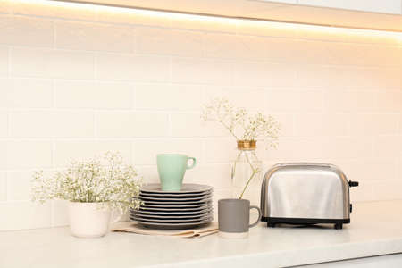 Modern toaster, crockery and flowers on counter in kitchen Stok Fotoğraf