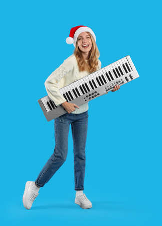 Young woman in Santa hat with synthesizer on light blue background. Christmas music
